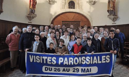 groupe-de-personnes-posant-avec-une-affiche-visites-paroissiales