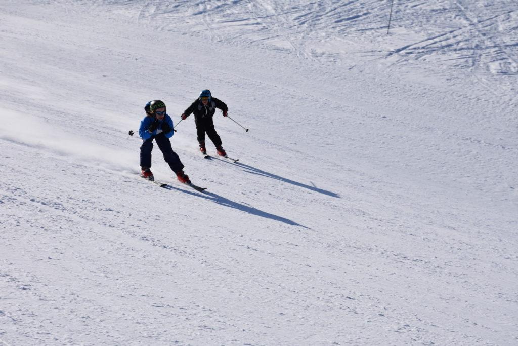 deux-personne-descendant-une-piste-de-ski