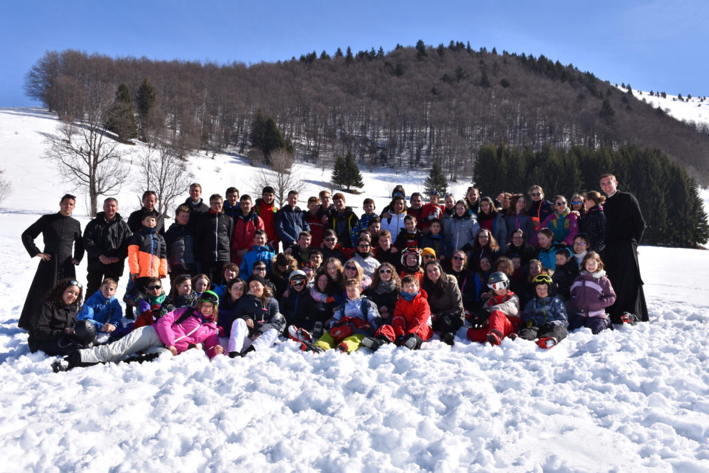 groupe-de-personne-posant-pour-la-photo-à-la-montagne-dans-la-neige