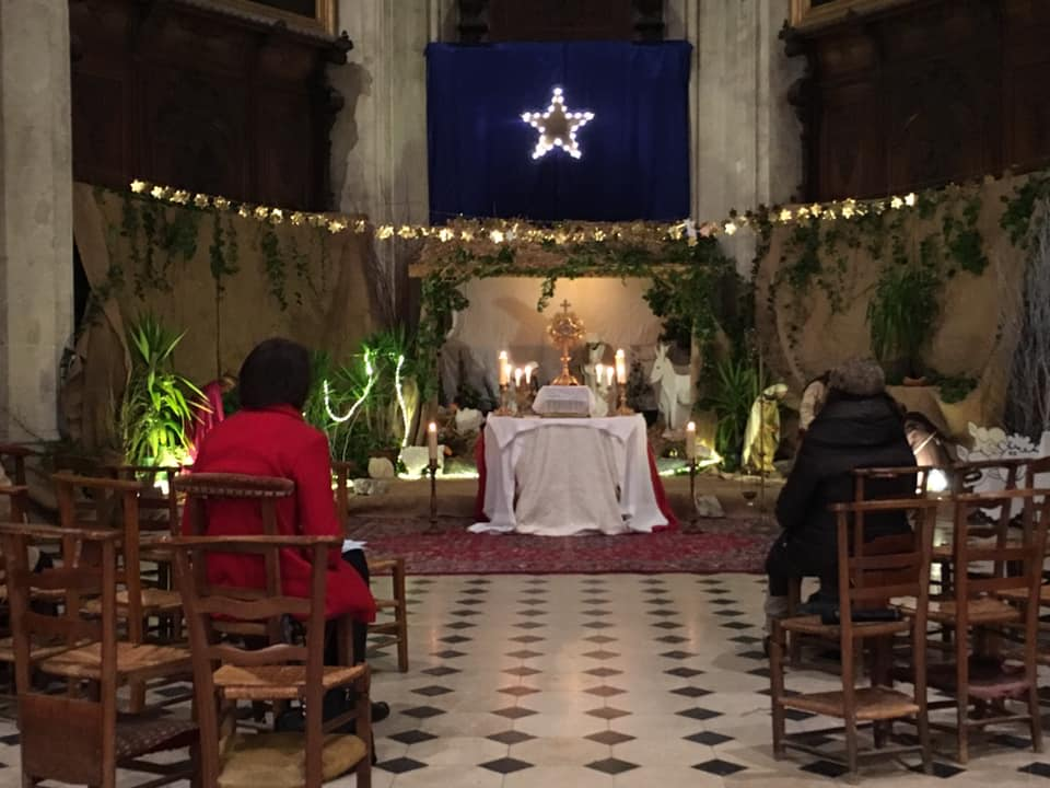 deux-personnes-priant-devant-la-crèche-de-église-sainte-céronne-au-perche